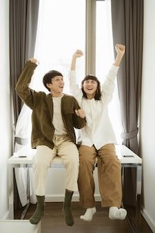 Jovem casal asiático dançando juntos em casa