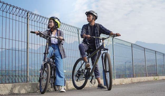 Jovem casal asiático descansando depois de andar de bicicleta vai para o trabalho