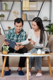 Jovem casal asiático discutindo itens que deseja comprar on-line por meio de um tablet e pagando com cartão de crédito