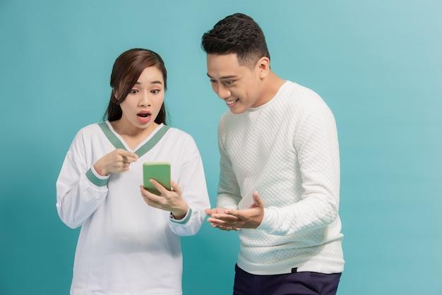 Jovem casal asiático em pé olhando para a tela de um telefone inteligente.
