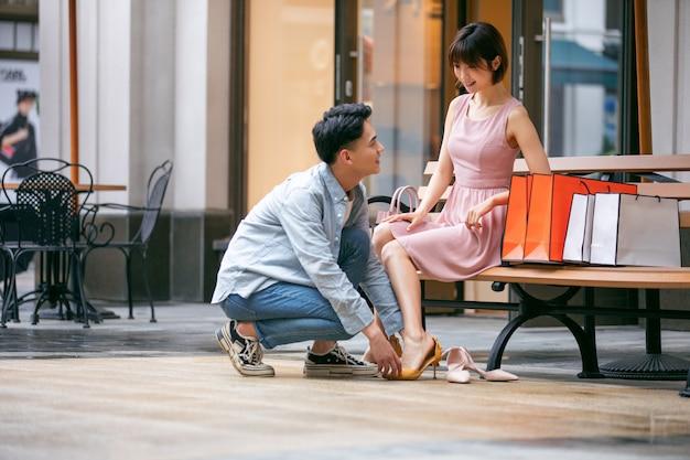 Jovem casal asiático experimentando sapatos