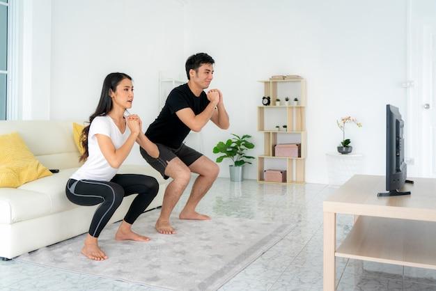 Jovem casal asiático fazendo agachamentos treinando juntos e olhando a tv em casa