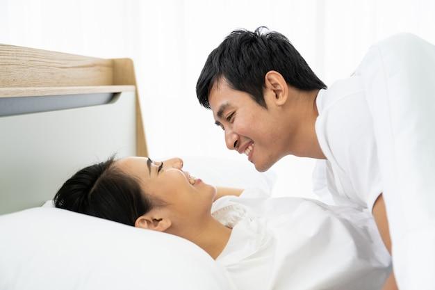 Jovem casal asiático fazendo amor juntos na cama.