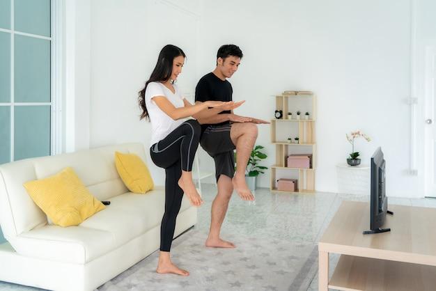 Jovem casal asiático fazendo treinamento intervalado de alta intensidade juntos e olhando a tv em casa