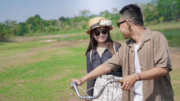 Jovem casal asiático feliz andando de bicicleta no parque no verão