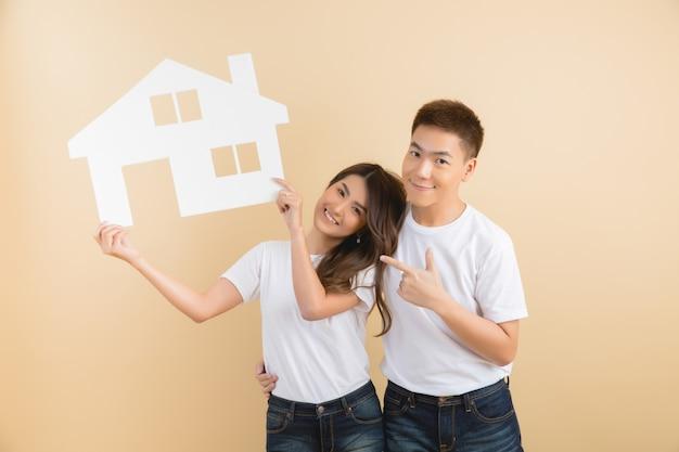 Jovem casal asiático feliz apresentando os símbolos da casa