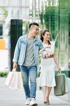 Jovem casal asiático feliz com sacolas de compras, andando na rua e discutindo roupas nas vitrines