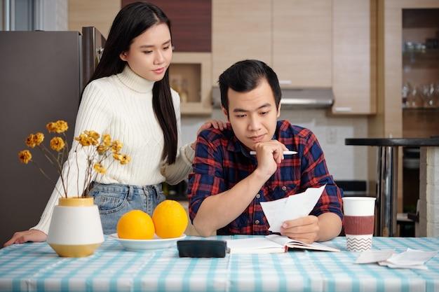 Jovem casal asiático gerenciando finanças domésticas, verificando impostos mensais, contas de pagamento com cartão de crédito e contas de serviços públicos
