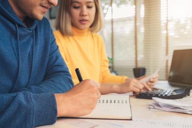 Jovem casal asiático gerenciando finanças, revendo suas contas bancárias usando o computador portátil