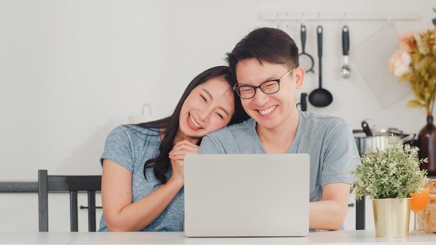 Jovem casal asiático gosta de fazer compras on-line no laptop em casa. estilo de vida jovem marido e mulher felizes compram comércio eletrônico depois de tomar café da manhã na cozinha moderna em casa de manhã.