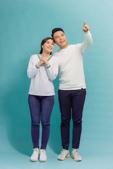 Jovem casal asiático isolado em azul apontando o dedo para o lado