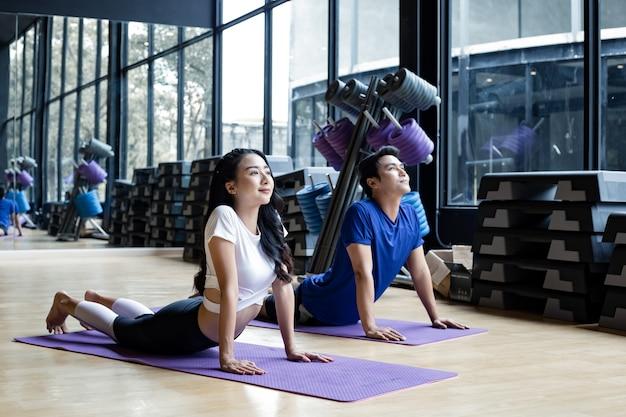 Jovem casal asiático jogando ioga de postura de cobra no tapete de ioga na sala de exercícios no ginásio com espaço de cópia. homem tailandês e mulher com exercícios fazendo ioga juntos no interior. exercício com o conceito de ioga.
