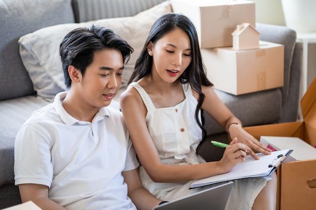 Jovem casal asiático lindo apaixonado, movendo-se para nova casa, sentada no chão, muito feliz e alegre para o novo apartamento em torno de caixas de papelão e segurando caixas de papelão enquanto se move para casa