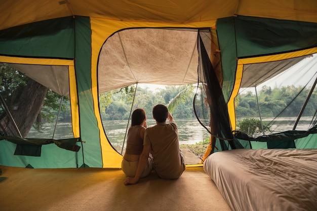 Jovem casal asiático relaxando em uma barraca em um acampamento no parque natural à noite