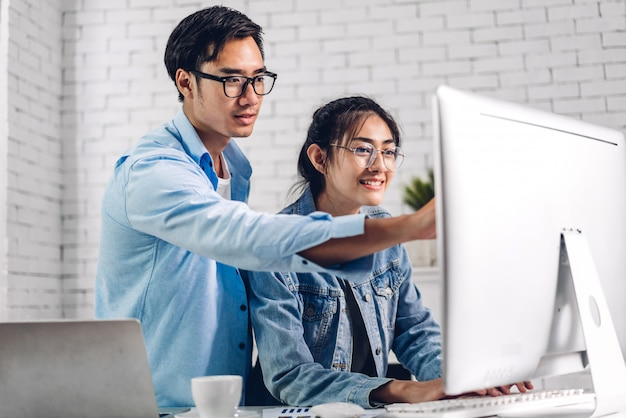 Jovem casal asiático relaxante usando o computador desktop trabalhando e videoconferência reunião bate-papo on-line. casal de negócios criativos planejamento e brainstorm em casa. trabalho do conceito de casa