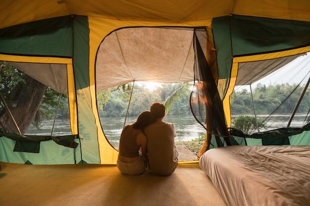 Jovem casal asiático se abraçando e relaxando dentro de uma barraca em um acampamento no parque natural à noite