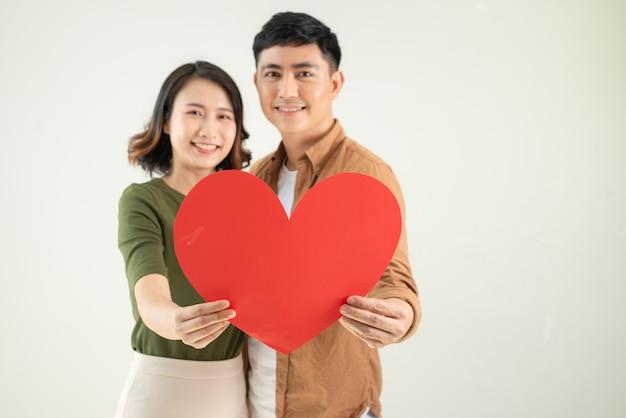 Jovem casal asiático segurando um adesivo de coração