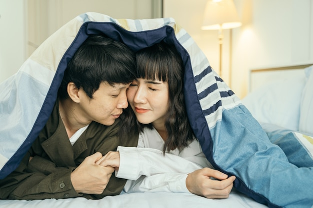 Jovem casal asiático sorrindo juntos debaixo do cobertor