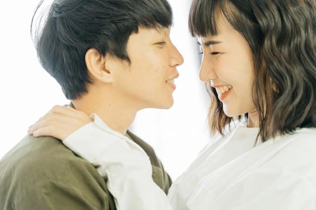Jovem casal asiático sorrindo juntos feliz em branco