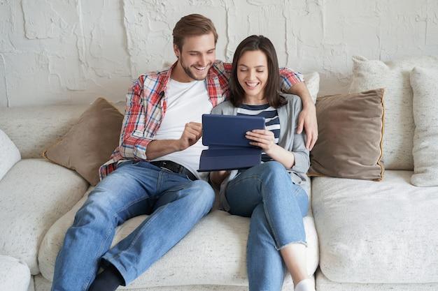 Jovem casal assistindo conteúdo de mídia online em um tablet sentado em um sofá na sala de estar.
