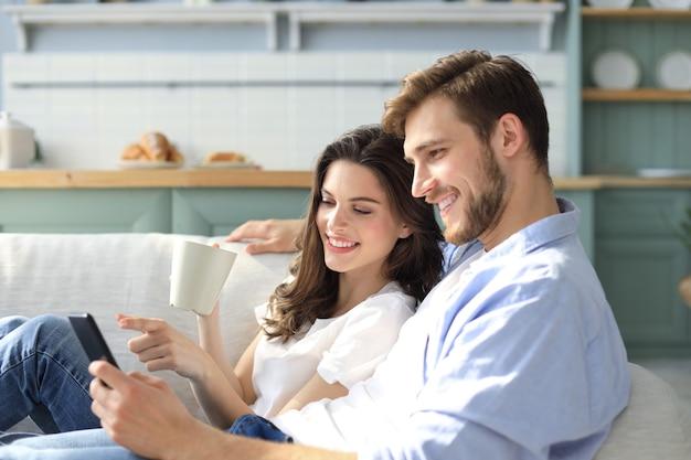 Jovem casal assistindo conteúdo online em um telefone inteligente, sentado em um sofá em casa na sala de estar.