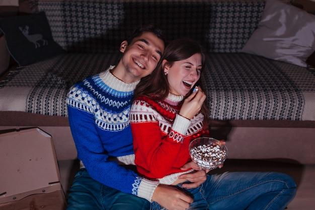 Jovem casal assistindo filme comendo pipoca em casa à noite