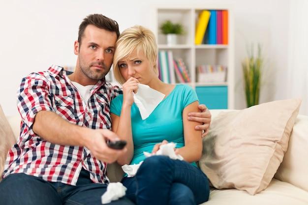 Jovem casal assistindo filme triste