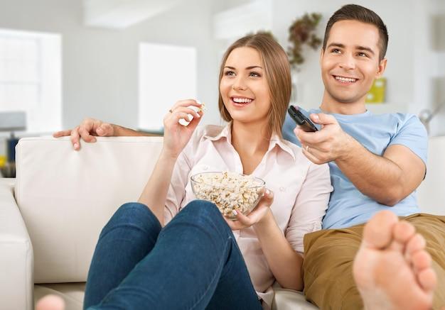 Jovem casal assistindo tv em casa