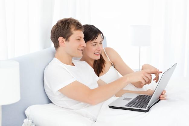 Jovem casal assistindo vídeos em seu computador em casa