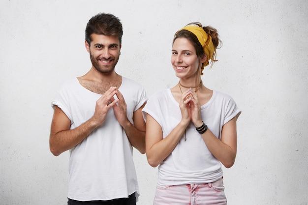Jovem casal astuto e astuto sorrindo misteriosamente, apertando as mãos, tramando ou planejando algo