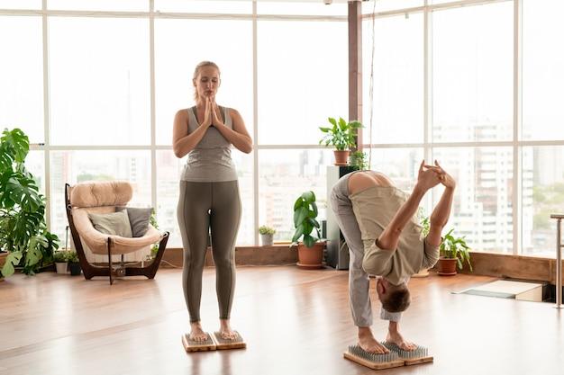 Jovem casal ativo descalço em roupas esportivas, de pé sobre almofadas de terapia de ioga com cerdas metálicas, enquanto se exercitam juntos em uma sala ampla