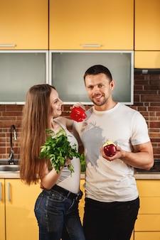 Jovem casal atraente dançando na cozinha. homem e mulher segurando frutas e legumes. conceito de comida saudável. dieta para a família, estilo de vida saudável