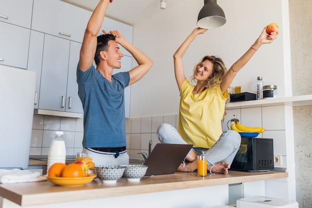 Jovem casal atraente de homem e mulher cozinhando o café da manhã juntos pela manhã na cozinha