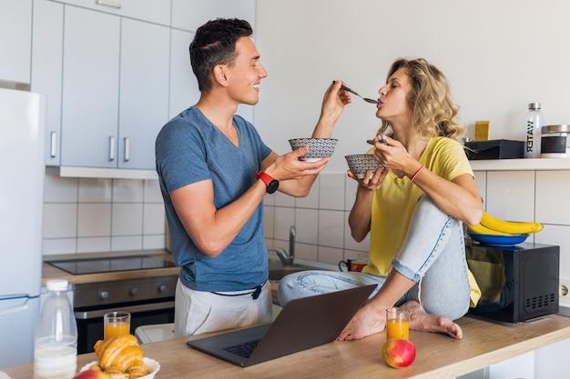 Jovem casal atraente de um homem e uma mulher apaixonada tomando café da manhã juntos na cozinha