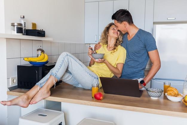 Jovem casal atraente de um homem e uma mulher tomando café da manhã juntos pela manhã na cozinha