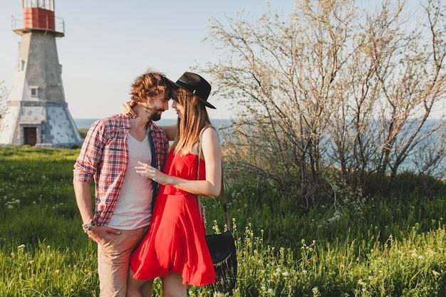 Jovem casal atraente e elegante apaixonado no campo, estilo indie hippie boêmio, férias de fim de semana, roupa de verão, vestido vermelho, grama