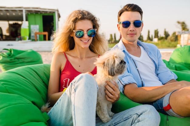 Jovem casal atraente e sorridente se divertindo na praia, brincando com o cachorro da raça shih-tsu, sentado em um saco de feijão verde