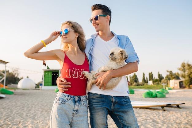 Jovem casal atraente e sorridente se divertindo na praia, brincando com o cachorro
