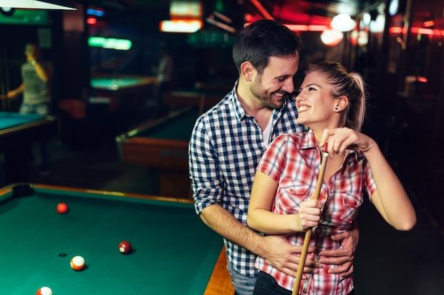 Jovem casal atraente em um encontro no clube de sinuca