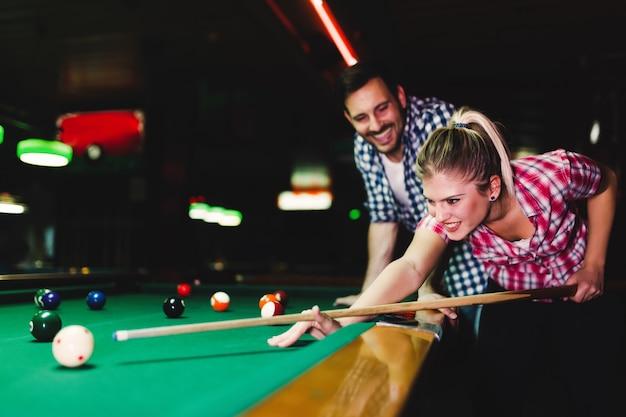 Jovem casal atraente jogando sinuca em bar