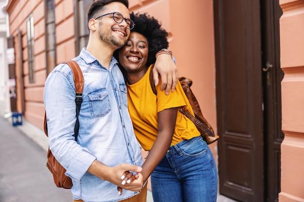 Jovem casal atraente multicultural abraçando e andando na rua.