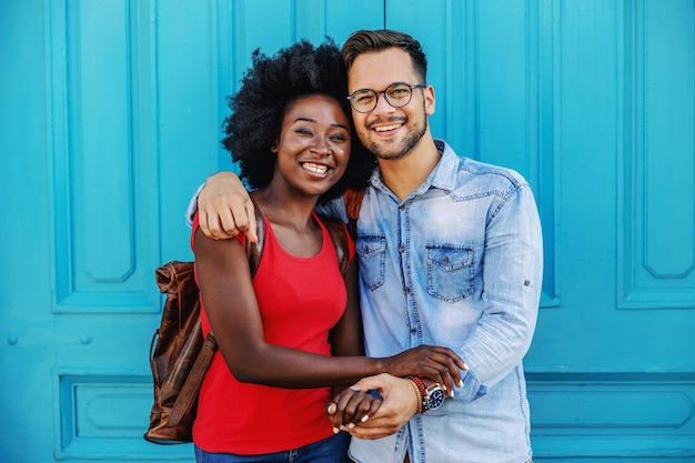 Jovem casal atraente multicultural apaixonado em pé ao ar livre e de mãos dadas.