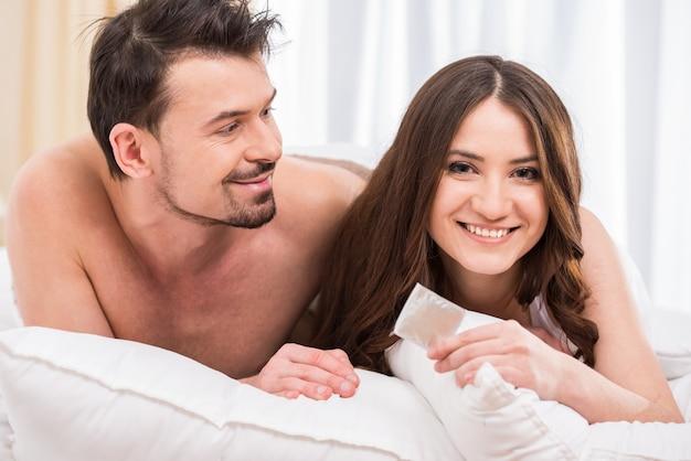 Jovem casal atraente na cama com um preservativo.