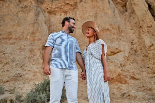 Jovem casal atraente no fundo das rochas está de mãos dadas e se divertindo. uma mulher de chapéu e vestido e um homem de camisa e calça branca estão descansando.