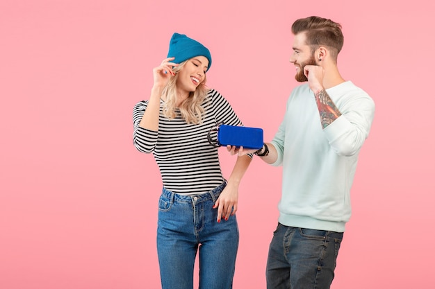 Jovem casal atraente ouvindo música no alto-falante sem fio, vestindo uma roupa elegante e legal, sorrindo, feliz humor positivo, posando em fundo rosa