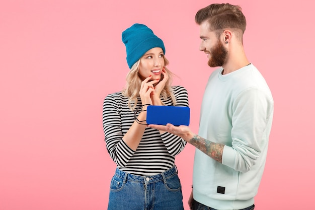 Jovem casal atraente ouvindo música no alto-falante sem fio, vestindo uma roupa elegante e legal, sorrindo, feliz humor positivo, posando na parede rosa isolada.