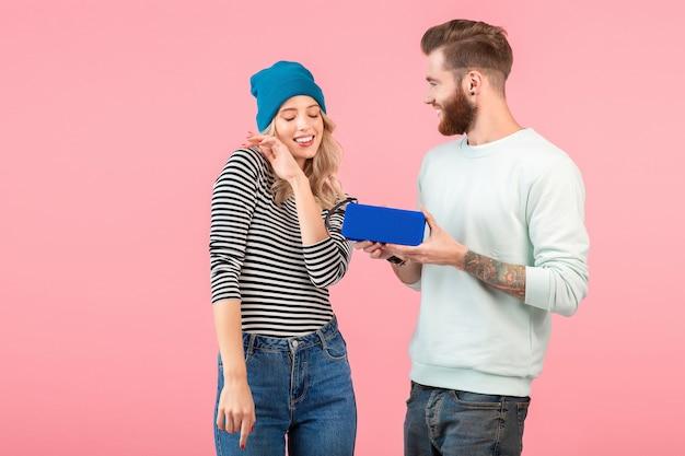 Jovem casal atraente ouvindo música no alto-falante sem fio, vestindo uma roupa elegante e legal, sorrindo, humor positivo e feliz, posando na parede rosa isolada dançando se divertindo