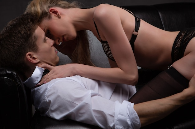 Jovem casal atraente se beijando em um abraço apaixonado enquanto estava deitado no sofá