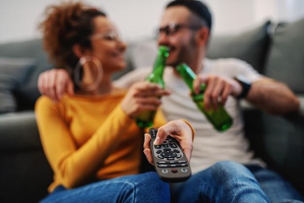 Jovem casal atraente sentado em casa, brindando com cerveja e assistindo televisão.