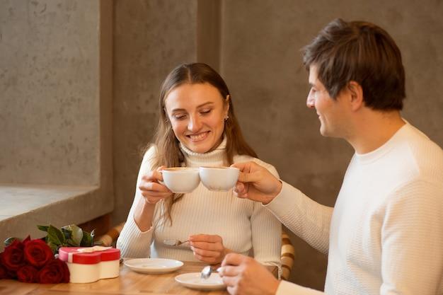 Jovem casal bebe café. bouquet de rosas e presente. namoro de namorados.
